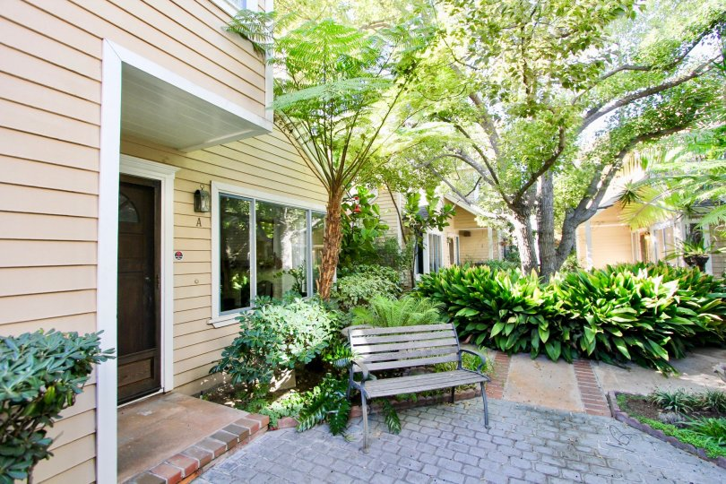 Quiet cozy courtyard with mature trees for shade and brick laid walkways in Hillcrest