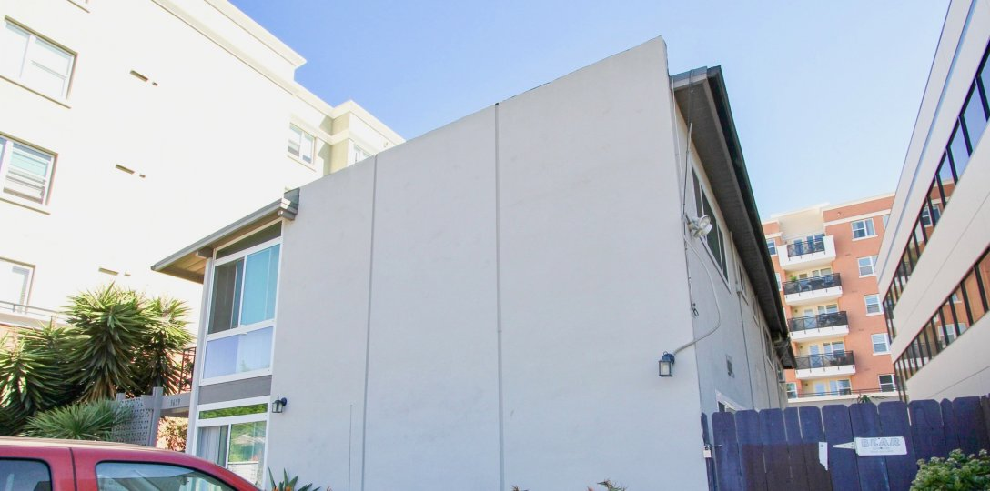 There is a bright open blue sky with a close up of a building's side. The building is cream colored and has three panels.