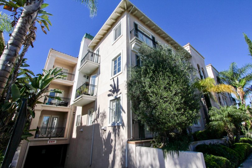 Ample of sunshine with palm trees in front of a multi story villa in Villa Portofino of Hillcrest