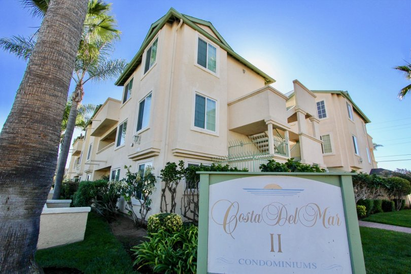 Three story housing behind community sign at Costa Del Mar II in Imperial Beach California