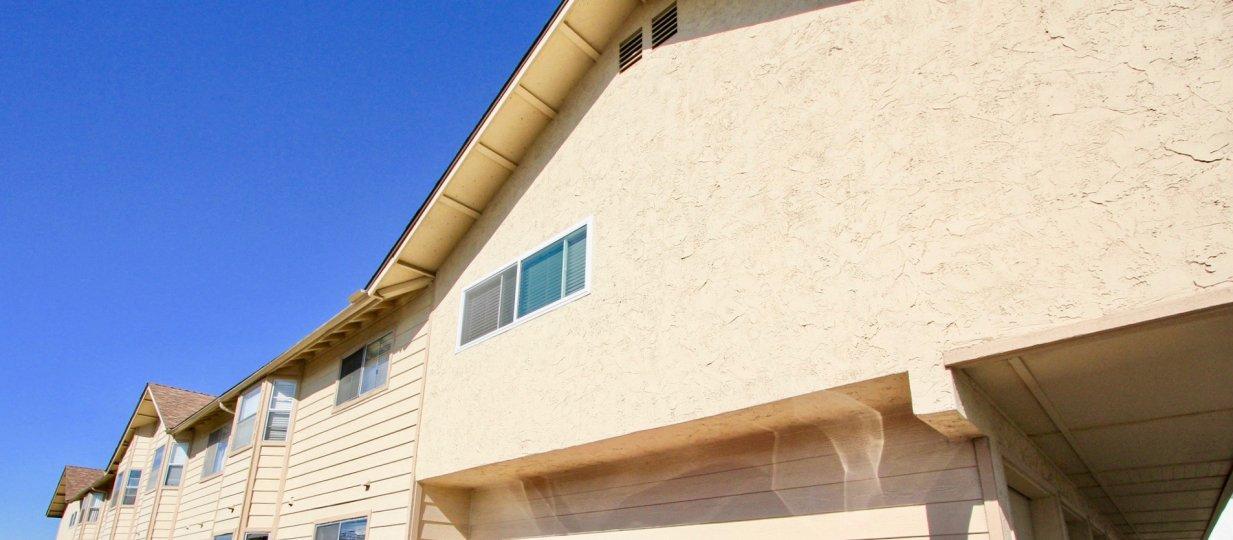 Top of beige building front with multiple windows, beige in color