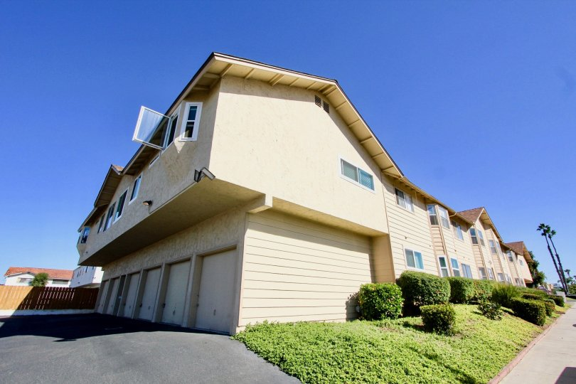 Two story housing with white garage doors near a green hillside in Holly Manor in Imperial Beach CA