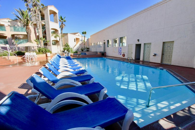 Swimming pool with lawn chairs near residence at Imperial Beach Club in Imperial Beach California