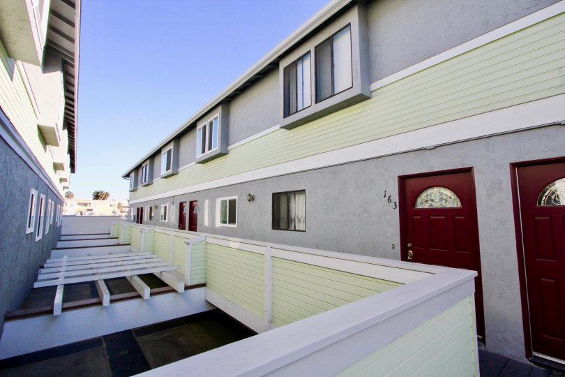 Residential units with reddish brown doors at Palm Plaza in Imperial Beach CA