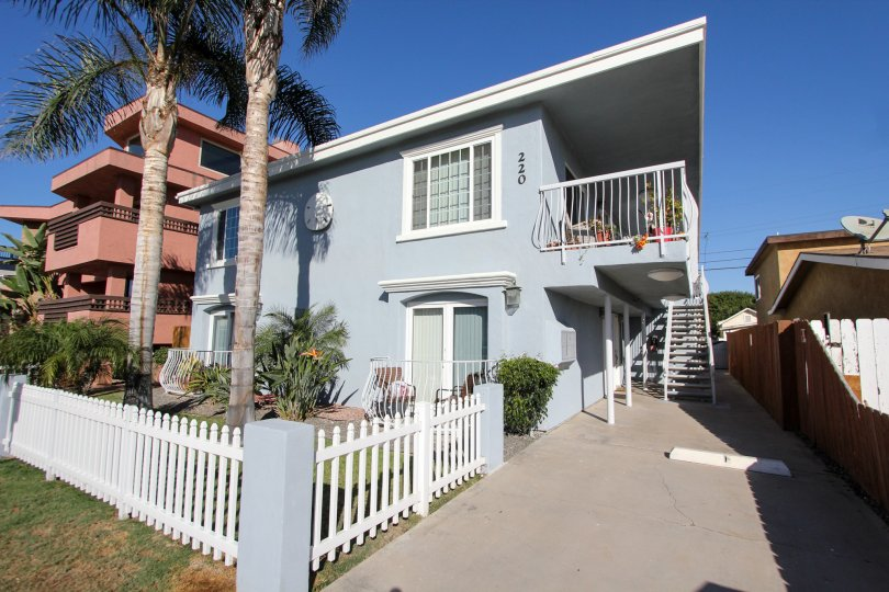Blue condominiums with balconies and walkway at Shauna Shores in Imperial Beach CA