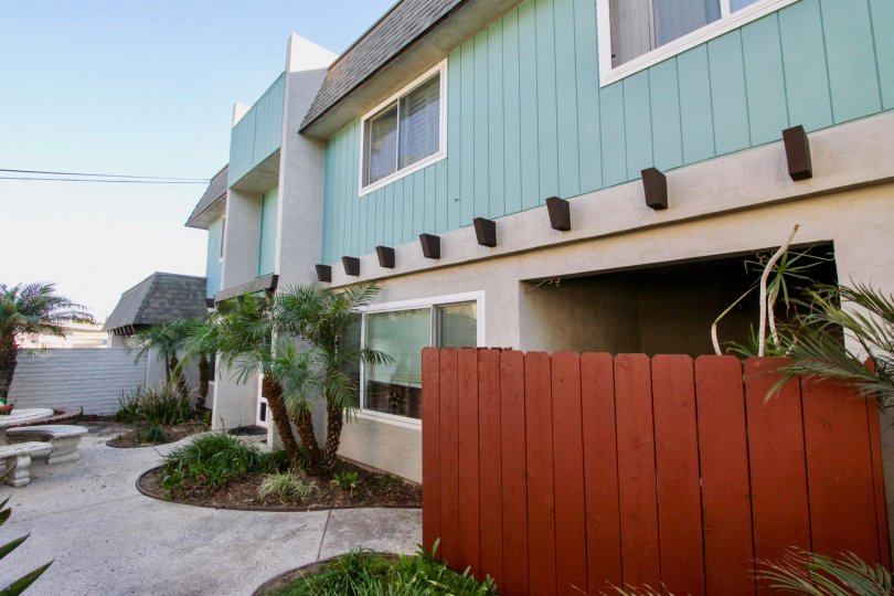 Blue green building with red wooden fence and palm trees, curved flower beds with mulch