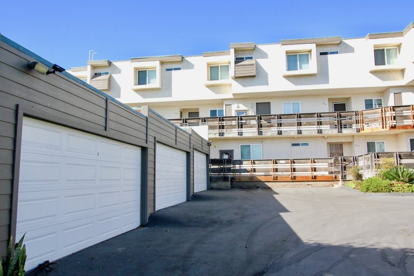 Three white garages inside of a single story gray structure in Imperial Beach CA at Vista De Coronado