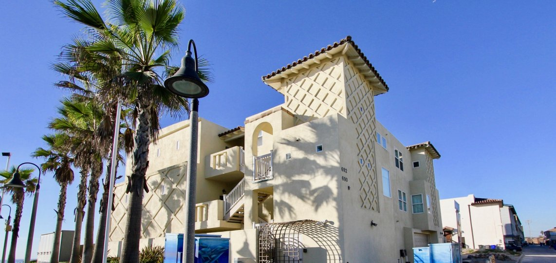 Three story residential building near palm trees at Wavecrest in Imperial Beach California