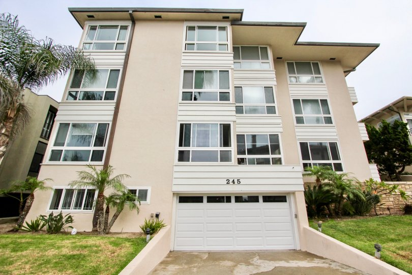 The apartment of 245 coast in La jolla city has grass and plants aside of the parkway