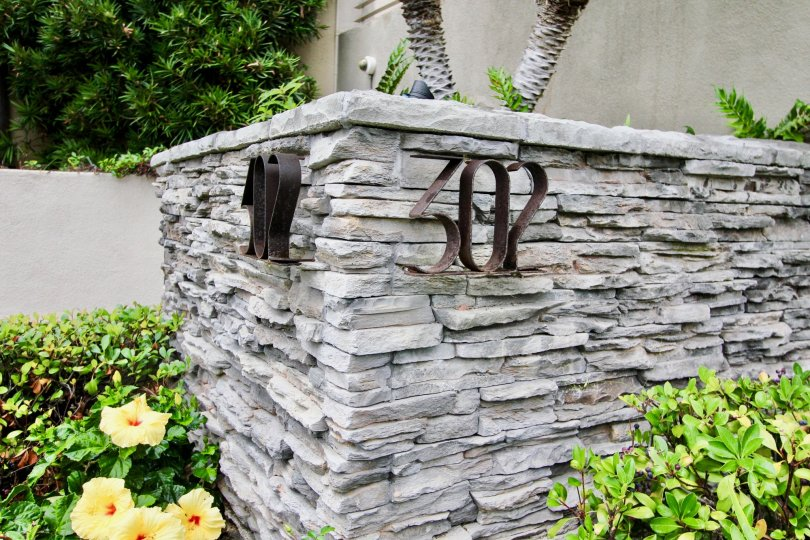Large gray stone wall with address outside of 302 Prospect in La Jolla CA