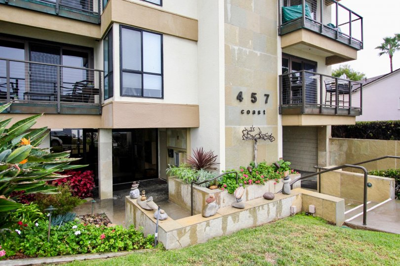 Three story housing with walkway lined with plants at 457 Coast in La Jolla California