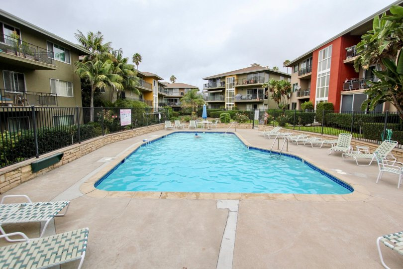 Pool surrounded by condos and furniture at Capri Aire in La Jolla CA