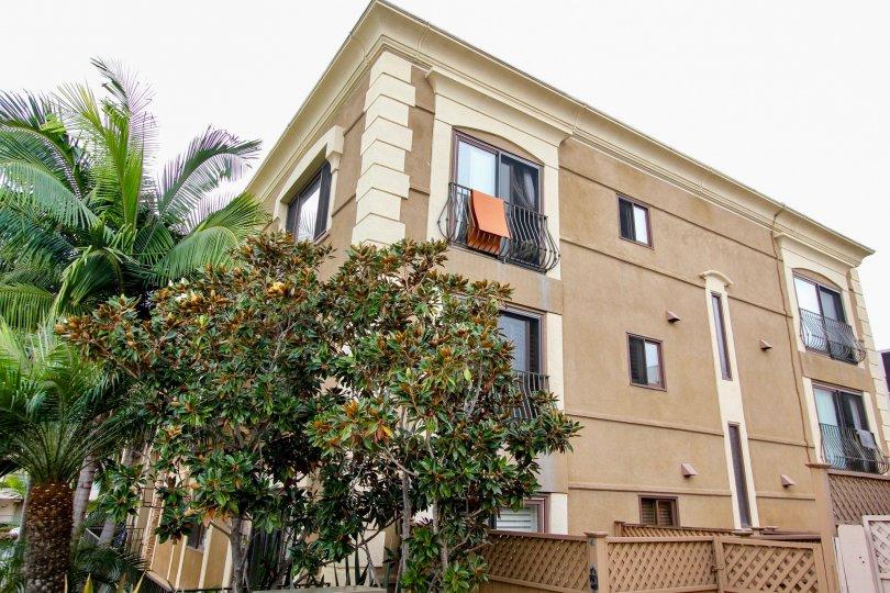 Three brown residential building with black railing at Chiara in La Jolla CA