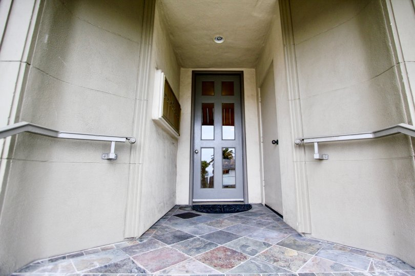 Glass and wood door with marble walkway at Coast Pointe in La Jolla CA