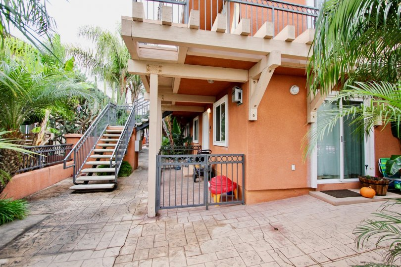 Two story pink housing with stairways & palm trees in Herschel Estates in La Jolla CA