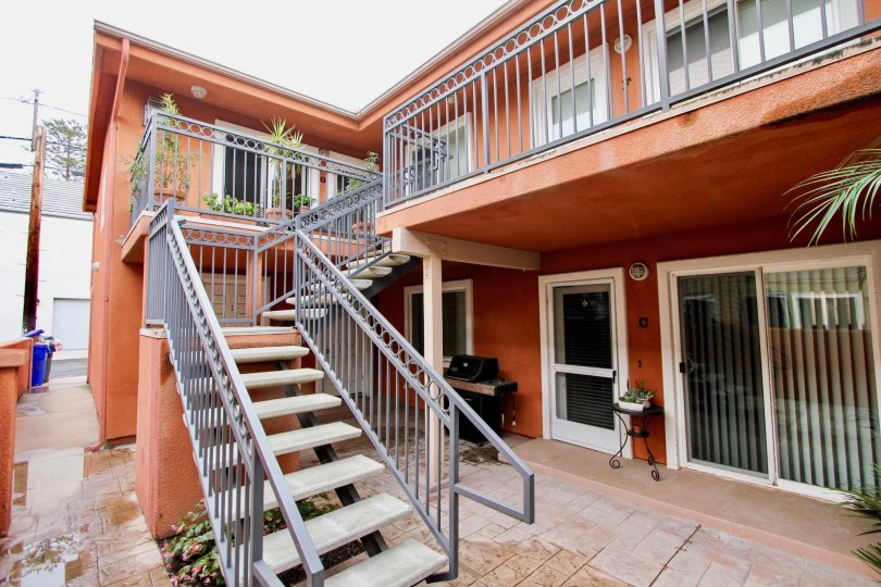A orange apartment with iron stairs leading to the balcony filled ith plants. there is an bbq downstairs