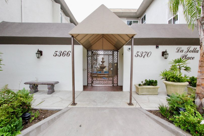 An entrance to the community La Jolla Place with a triangular roof.