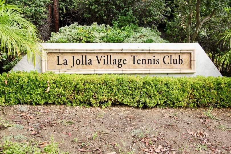 The wall in the La Jolla Village Tennis club is surrounded with Bushes and trees