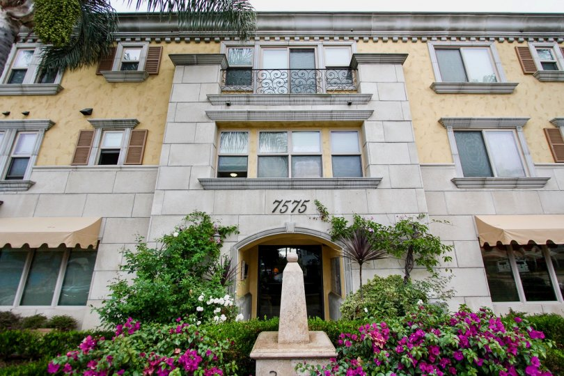 A three story, upscale aparment building surrounded by colorful flowers, built in an antique design, located in the Montrachet community.