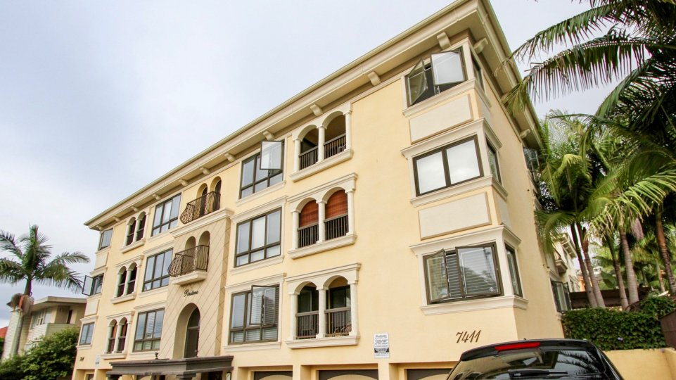 A beautiful multi floor building with palm trees surround in Positano community.