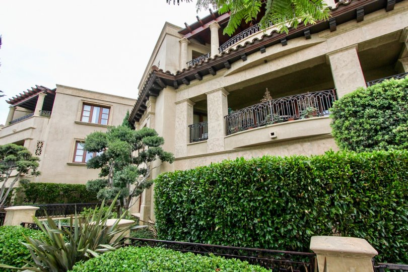 Three story housing with a large green bush & plants in Prospect Point Villas in La Jolla CA
