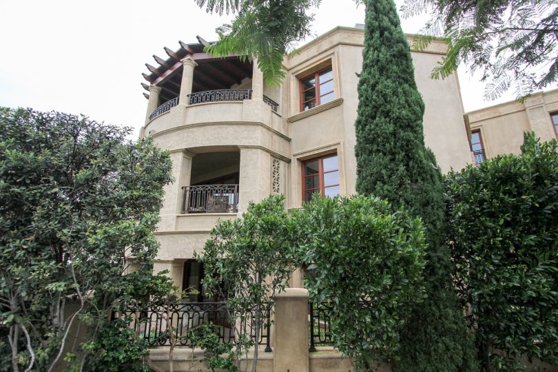 This three story house is located in Prospect Point Villas and is surrounded by bushes and trees.