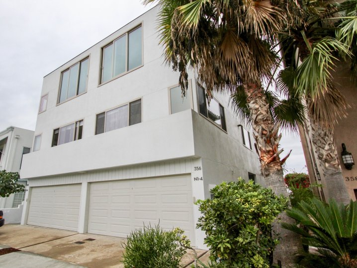 Two large gray garages at the base of a building in Prospect Terrace in La Jolla CA