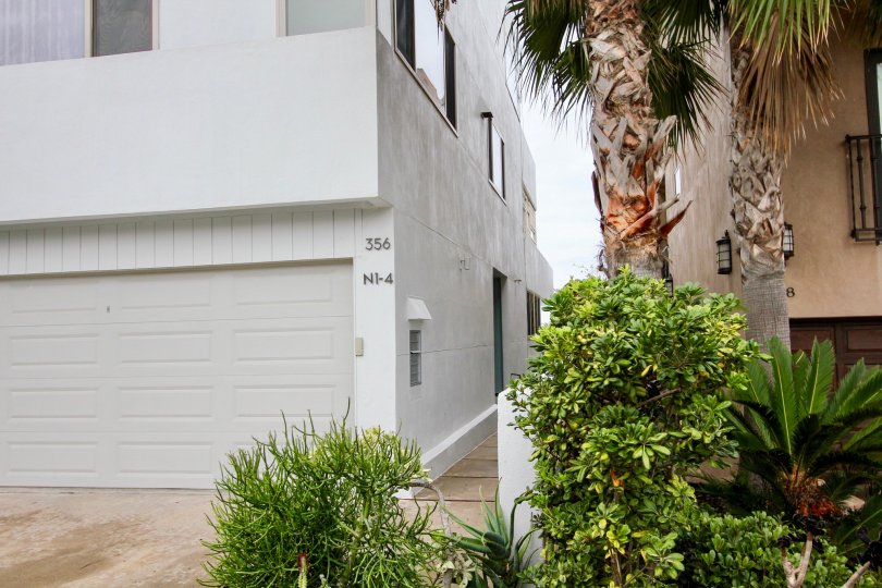 A gray house with a big garage door and some palm trees and bushes at the front in Prospect Terrace, La Jolla, CA