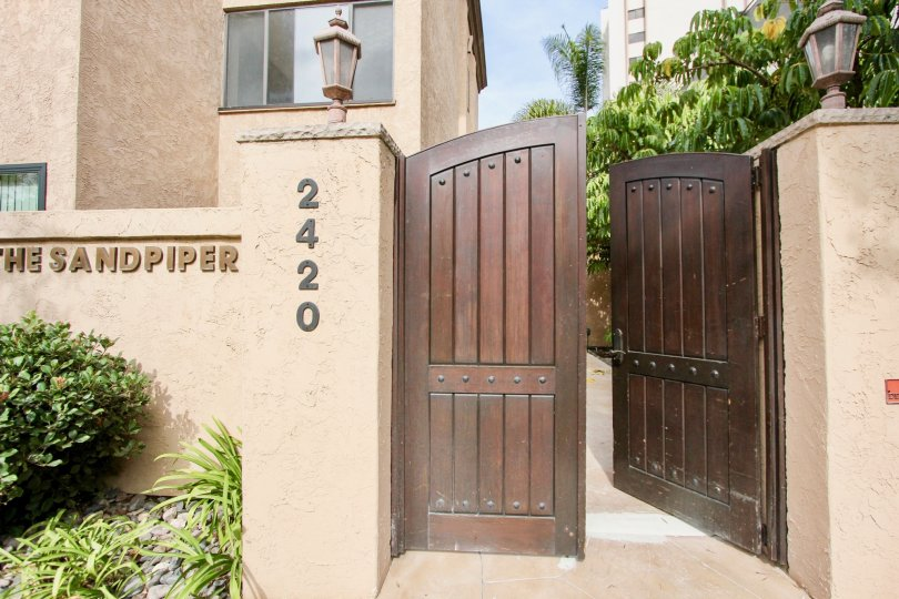 Ornate double door entrance with high privacy fences and decorative light sconces in La Jolla