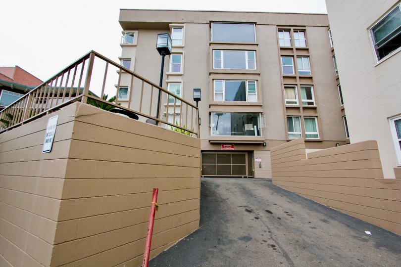 A five story apartment complex with big windows in an urban area. The picture was taken from a back alley