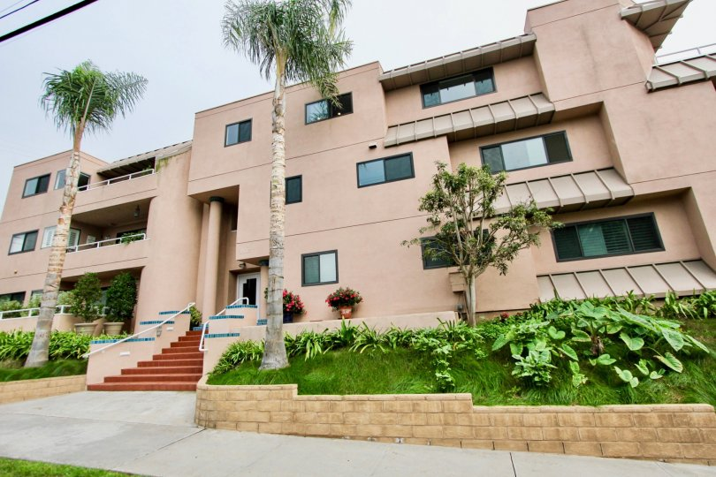 Three story pink building with grass & plants in Villa Italian community in La Jolla CA