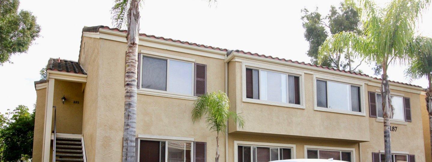 Two story white building with windows & palms in Villa Tuscana in La Jolla California