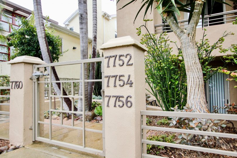 Gateway entrance with multiple address numbers at Village Walk in La Jolla CA