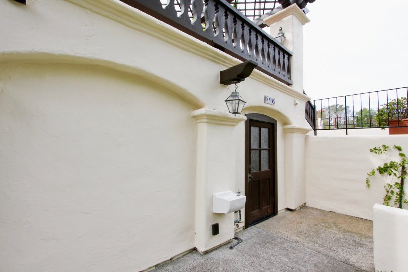 Black door next to a hanging lantern and wall at Villas Mailorca in La Jolla CA