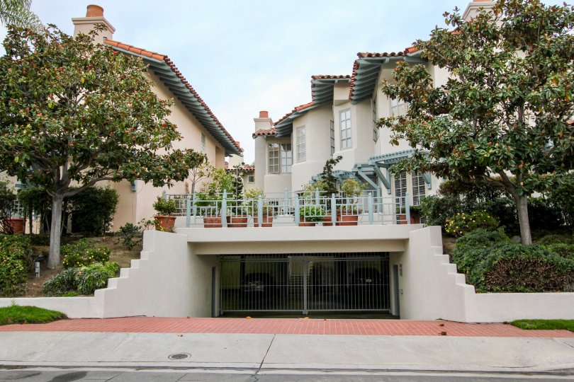 A street view of the Villas of Ivanhoe that displays the parking garage and garden in La Jolla, California.