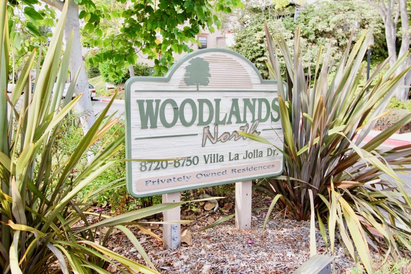 Wooden sign with green and pink writing inside Woodlands North in La Jolla CA