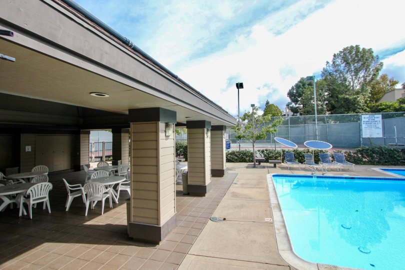 A sunny day poolside in the area of Woodland West I, outsidem picnic tables, beach chairs, trees, fence