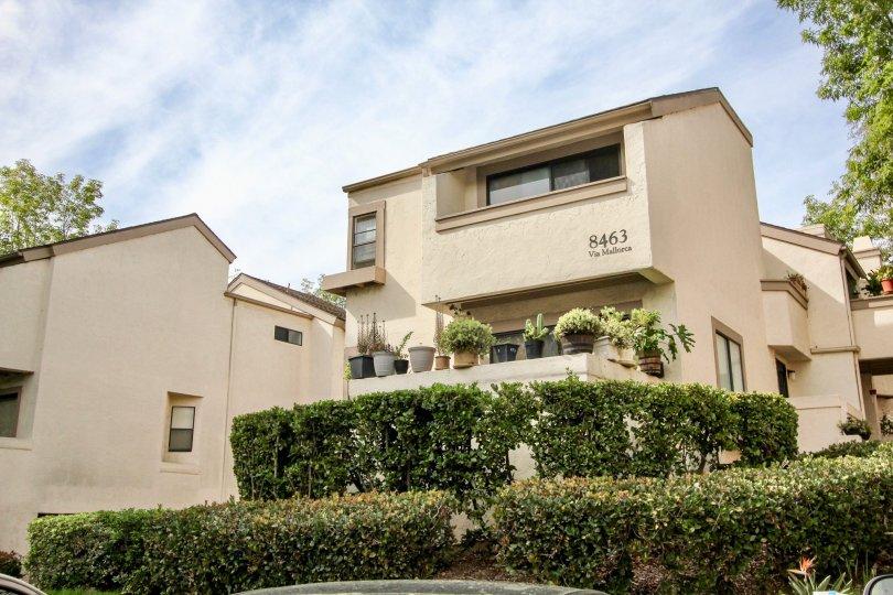 The beautiful, beige colored apartment complex of Via Mallorca located in the Woodlands West l community of La Jolla, California