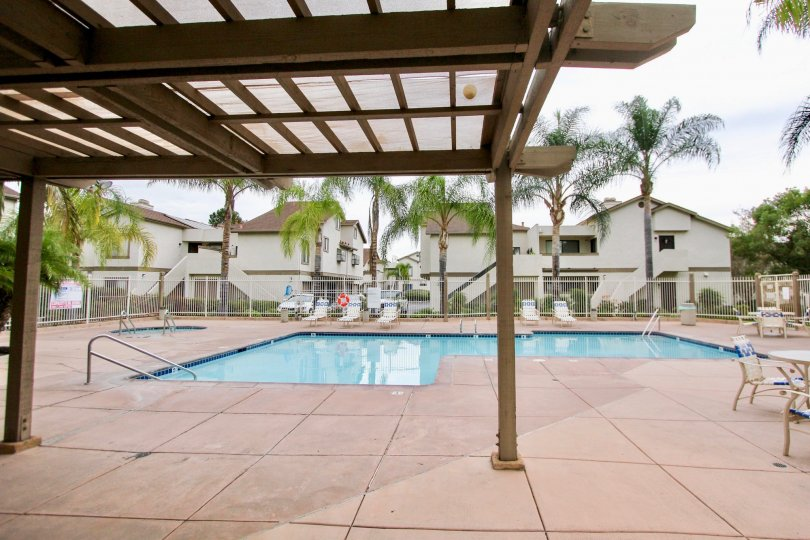 A panoramic view of a backyard swimming pool in La Mesa, CA, taken from beneath a wood-slat awning.
