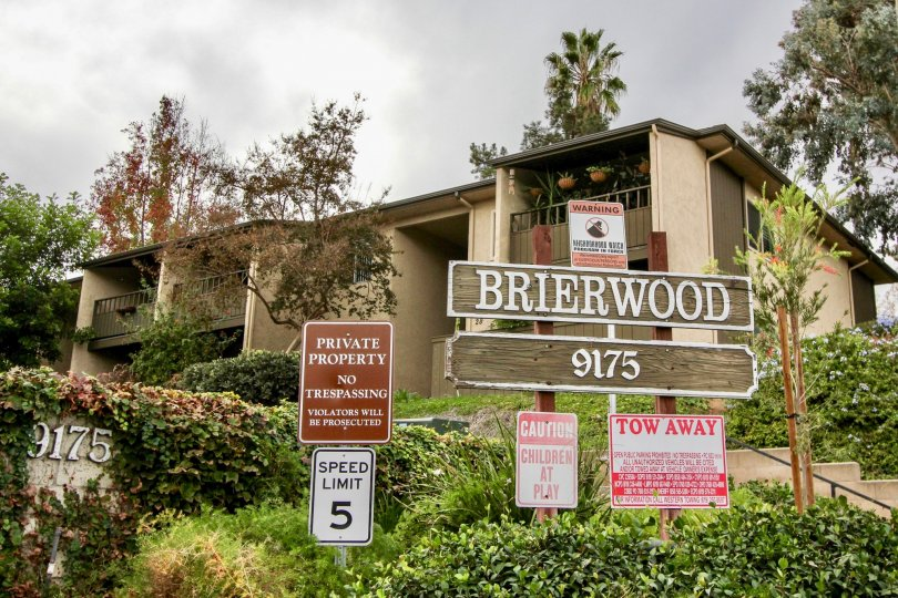 a wooden board of Brierwood Village with the housing and green bushes running behind it