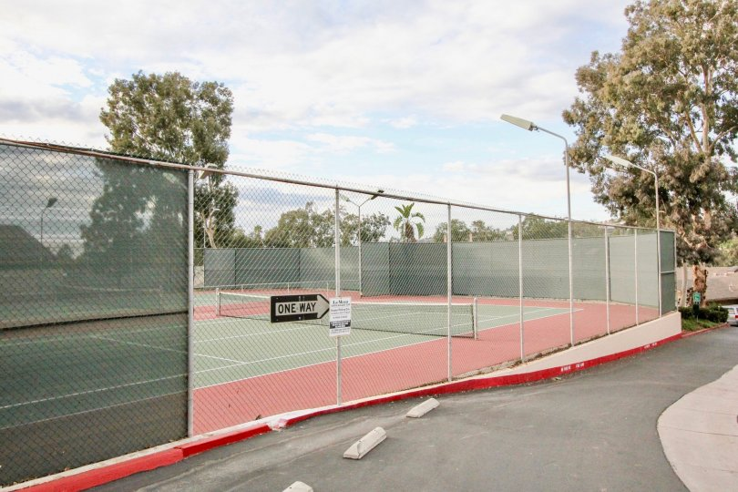 Black & white sign pointing to the right at a tennis court in La Mesa Racquet & Swim Club in La Mesa CA
