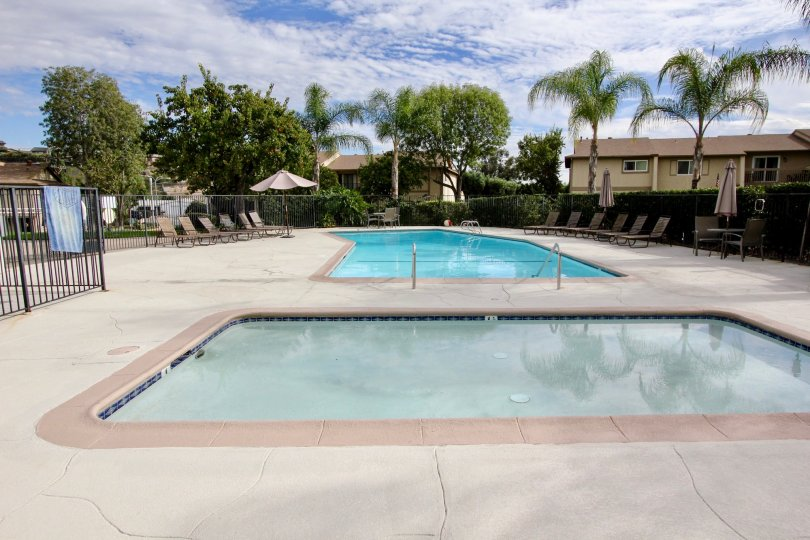 Nice swimming pools on a sunny day in between villas with palm trees in Lake Glen Park of La Mesa