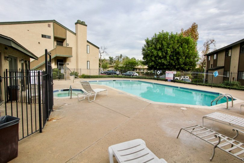 Private fenced in swimming pool for residents with adjacent soaking pool and deckside chairs in La Mesa