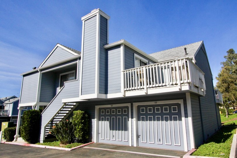 A two story blue home with white trim & chimney in Mira Mesa CA at Canyon Colony