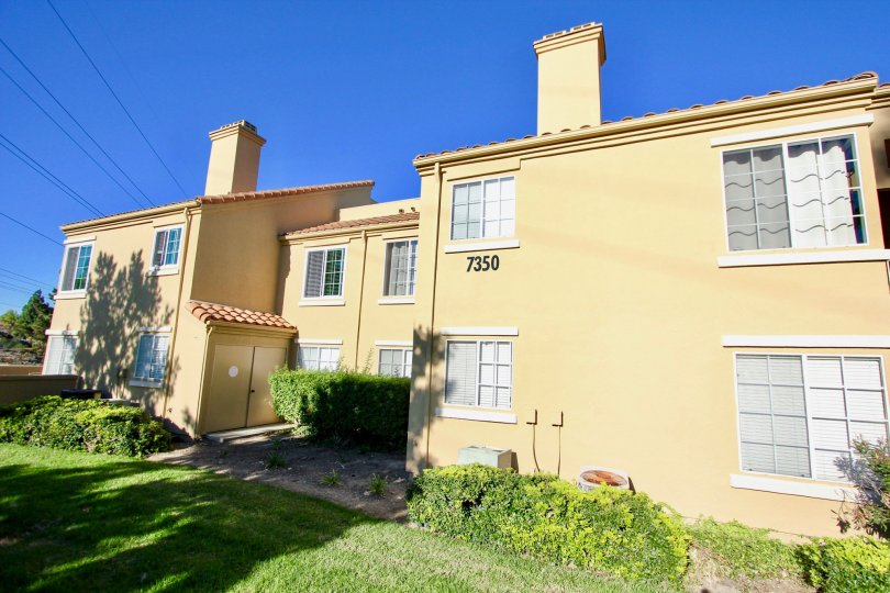 Two story residential units next to green yard at Canyon Park Villas in Mira Mesa California