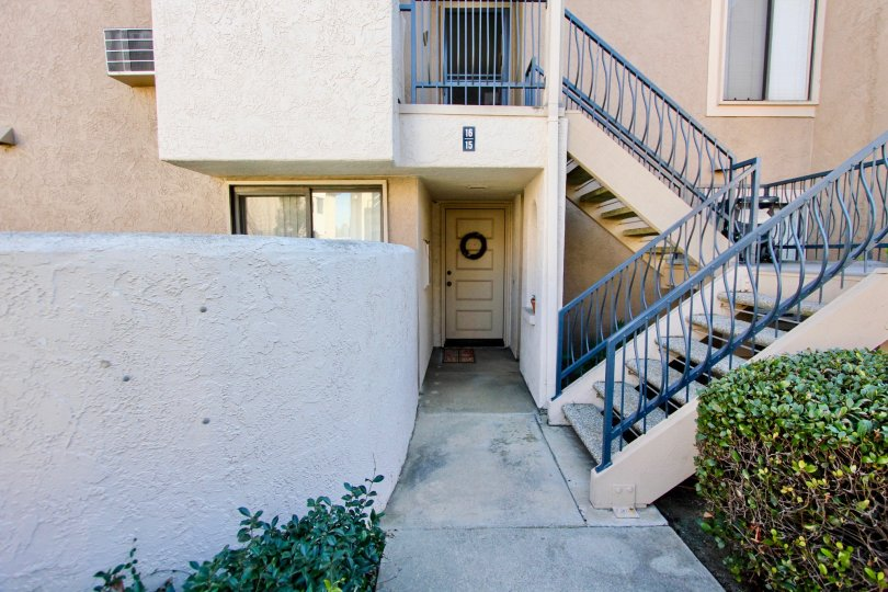 A front wooden door of a house in an apartment building with a stairs in front of it at Flair community