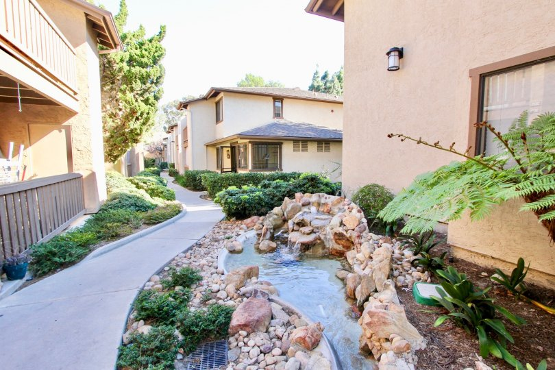 Beautiful artificial water stream in between villas with green trees in Quail Creek of Mira Mesa