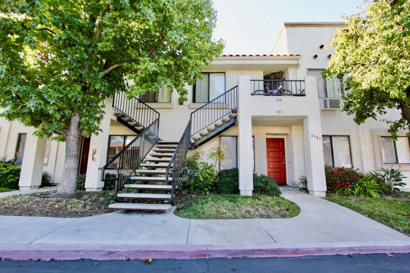 Sunny day trees with front staircase of a residence house in Villas at Capricorn, Mira Mesa, CA