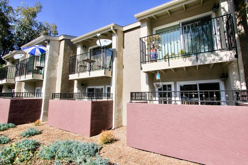 A residential building with pink walls around it's patios at Windsor Park in Mira Mesa CA