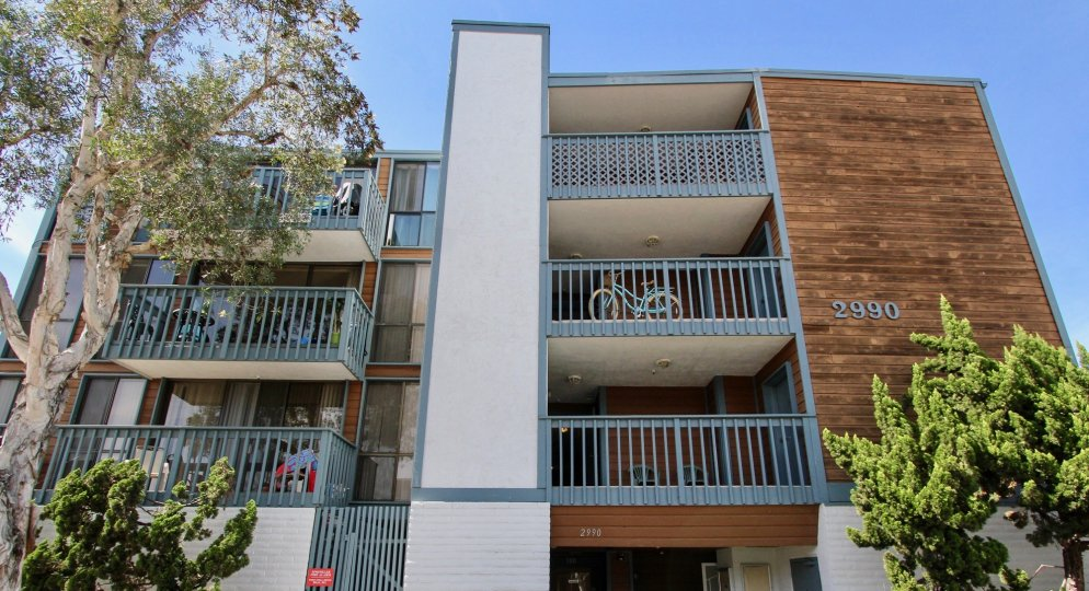 A sunny day including front view of three story apartment in 2290 Mission with trees and bycyle